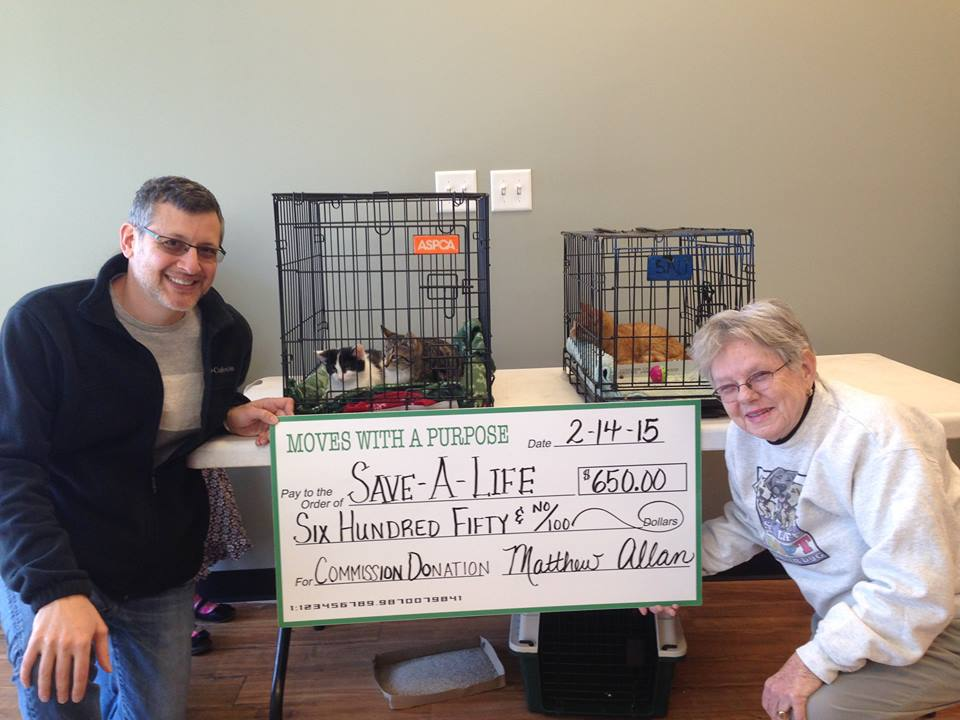 Mathew Allen of Keller Williams Realty Savannah Downtown presents a donation check to Julie Blocker for Save-A-Life.  At Keller Williams 10% of their sales goes to the charity selected by the purchaser.  Dr. Steve Goldberg bought a new office space for his chiropractic practice and selected Save-A-Life. Several of our adoptable pets look on!